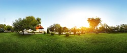 Panorama of a green garden with buddhist building and meadow with grass at early morning