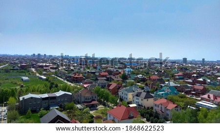 Panorama of a Krasnodar dormitory town from under the blue sky in spring. Spring in a southern dormitory suburb. Krasnodar outskirts on a sunny day. Tree-lined streets with houses of a bedroom suburb. Foto d'archivio ©