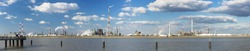 Panorama of a large refinery area with tall flare stacks in the port of Antwerp, Belgium with lots of distillation towers.