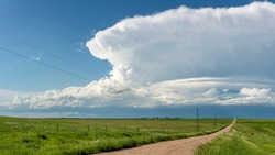 Panorama of a massive storm system, which is a pre-tornado stage, passes over a grassy part of the Great Plains while fiercely trying to generate more energy.