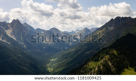 Panorama of a mountain valley with various trees along the hillsides and distant peaks in the horizon. #1181009425