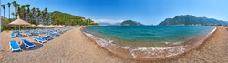 Panorama of a sandy beach without people and with sun loungers, umbrellas, palm trees, Marmaris, Turkey,