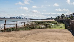 Panorama of a slipway leading down to the River Mersey at low tide.  The famous skyline of Liverpool can be seen in the background in the summer sunshine.