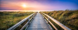 Panorama of a wooden pier along the dunes during sunset