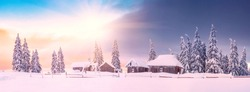 Panorama of abandoned mountain village in high mountains. Bright winter scene of Carpathians. Evening in mountain valley with snow covered fir trees. Christmas and New Year mood.