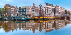 Panorama of Amsterdam canal Singel with typical dutch houses and houseboats during morning blue hour, Amsterdam, Holland, Netherlands.
