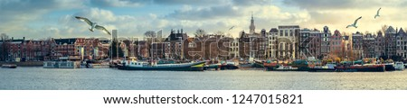 Panorama of Amsterdam old town on sunset - traditional Dutch houses, barge and houseboats on The Prins Hendrikkade street. Wide cityscape along quay in Oosterdok with the Montelbaanstoren tower.