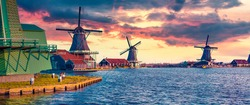 Panorama of authentic Zaandam mills on the water canal in Zaanstad village. Colorful spring sunset in  Netherlands, Europe. Artistic style post processed photo