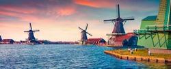 Panorama of authentic Zaandam mills on the water channel in Zaanstad village. Zaanse Schans Windmills and famous Netherlands canals, Europe. Instagram toning.