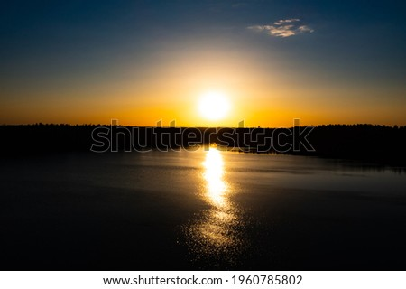 Panorama Of Autumn River Landscape In Belarus Or European Part Of Russia At Sunset. Sun Shine Over Blue Water Lake Or River At Sunrise. Nature At Sunny Morning. Woods With Orange Foliage On Riverside Foto stock ©