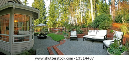 Panorama of backyard with patio set, chairs, and jacuzzi