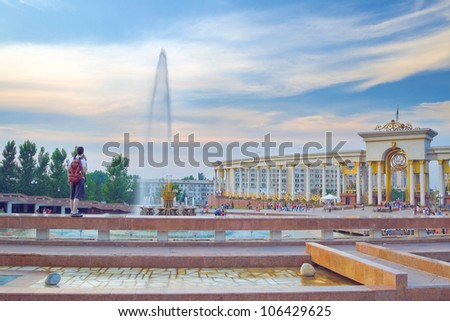 Panorama of big fountain in National Park of first President of Kazakhstan. Young tourist admiring the sunset scenery. Almaty