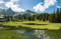 Panorama of Black Lake (Schwarzsee) marshland with summer vegetation in the mountain over the Walensee Lake, Switzerland