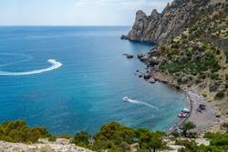 Panorama of Blue Bay near Novyi Svit, Crimea. Mountains are named Karaul Oba, short land in corner is so called Tsar Beach. Tourist boats are cutting waves of Black Sea