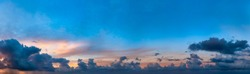 Panorama of blue sky with dark clouds on the horizon. Dramatic atmosphere preceding the storm. Cumulus formation. Threatening sky. Twilight colourful sunset. High resolution panoranic sky.