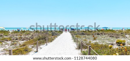 Panorama of Bowman's beach at Sanibel Island with sandy trail, path, walkway, fence, many people, crowd in distance, crowded coast, coastline shelling, looking for shells