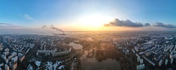 Panorama of Bucharest from a drone, districts of residential buildings with park and lakes, fog other the ground, Romania