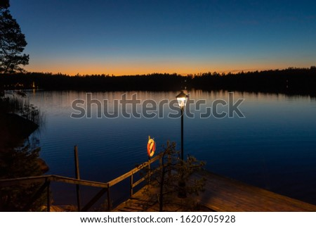 Panorama of calm water lake at sunset. Wooden descent into the water for swimming. Lifebuoy. Colorful skyline in orange and pink colors. Lights lanterns shine on the shore. Evening tranquil landscape