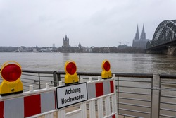 panorama of Cologne with cathedral and hohenzollern bridge at snowy weather. rhine river with high water, barrier with warning sign, german word for flood