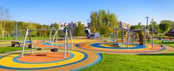 Panorama of colorful large playground in a city park. Empty modern outdoor playground in summer. Beautiful urban place for kids games and sport. Scenic view of children ground.
