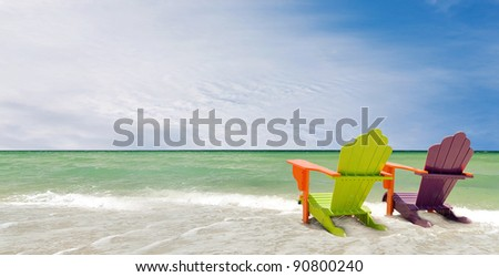 Panorama of colorful lounge chairs at a tropical beach in Miami Florida. Beautiful aqua green waters of the ocean and a blue sky  with clouds in the background
