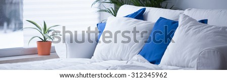 Panorama of comfortable bed with neat white and blue bedding