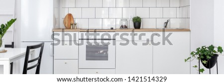 Panorama of contemporary kitchen with white cupboards and dining table #1421514329