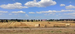 Panorama of country side across green grass field of cut and rolled hay near North Poland against dramatic clouds and blue sky. Country side background.