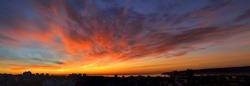Panorama of dawn fire in the sky over a small seaside city. Golden red clouds just before the sunrise. Scenic landscape at sunrise. Beauty in nature.