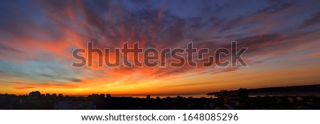 Panorama of dawn fire in the sky over a small seaside city. Golden red clouds just before the sunrise. Scenic landscape at sunrise. Beauty in nature. Photo stock ©