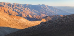 Panorama of dramatic golden sunset or sunrise light and shadow on the rugged terrain of the badlands landscape in Death Valley Park National Park, California, USA.