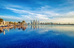 Panorama of Dubai Marina at sunset with a swimming pool in front
