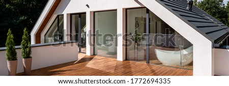 Panorama of elegant house balcony with wooden floor and with entrance from balcony window in attic bathroom with bathtub