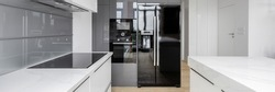 Panorama of exclusive kitchen with white furniture and countertops and gray backsplash tiles and big black fridge