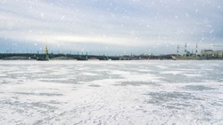 Panorama of famous tourist attraction Neva river covered with ice. With falling snow in winter on afternoon. Saint Petersburg in winter. Russia.