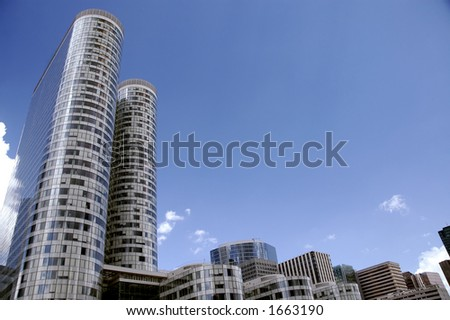 Panorama of few round skyscrapers over blue sky