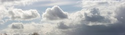 Panorama of fluffy cumulus and rain clouds drifting through dramatic cloud filled frame against a soft blue sky. Climate and weather concept. Detail natural phenomenon.