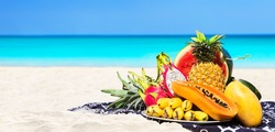 Panorama of fresh different tropical fruits placed on the beach with blue sky and sea background. Summer time beach concept of healthy eating.