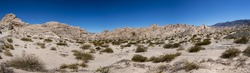 Panorama of geological rock formations and arid lunar landscape in the Andean Mountains, close to Rodeo. Blue sky in the background. Argentina
