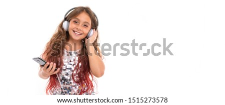 Panorama of girl with big white earphones listening to music, touching her left earphone and holding black smartphone isolated