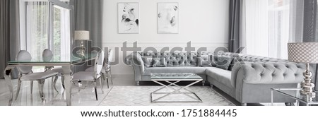 Photo of  Panorama of glamour designed living room in white and gray with elegant quilted corner sofa and glass dining table