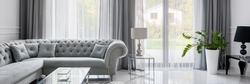 Panorama of glamour style living room with quilted corner sofa and glass coffee table