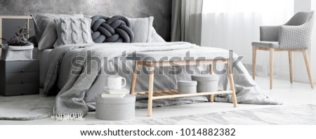 Panorama of grey bedroom interior with armchair and wooden bench next to a bed with cushions