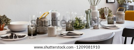 Panorama of grey table with wine glasses, candles and tableware in dining room interior. Real photo #1209081910