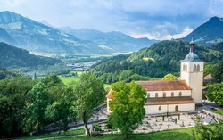 Panorama of Gruyeres town with Saint Theodule church and graveyard view and mountains in background in La Gruyere Fribourg Switzerland