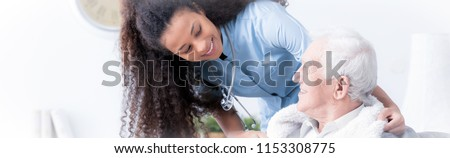 Panorama of happy caregiver supporting smiling elderly man in the nursing house