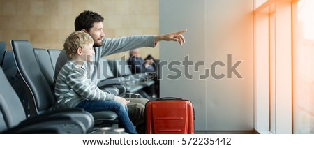 panorama of happy family of two, father and son, waiting together at the airport for plane departure with luggage, father pointing with finger at something, sun flare effect