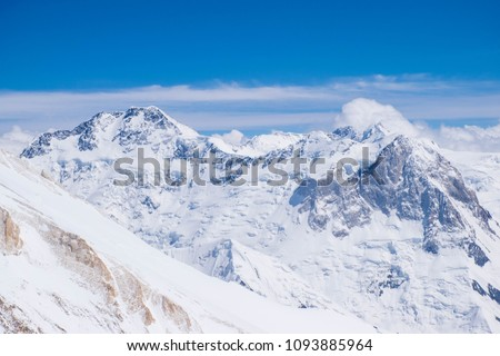 Panorama of high snow mountains in Central Asia with big rock walls and glaciers under the clouds in a cold summer day. Best place for active life, vacation, trekking, hiking and climbing.