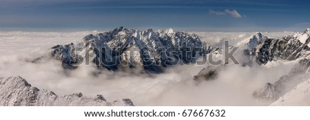 Panorama of High Tatras winter above the clouds. View from the summit Konczysta.
