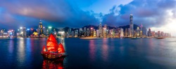 Panorama of Hong Kong City skyline with tourist sailboat at night. View from across Victoria Harbor HongKong.